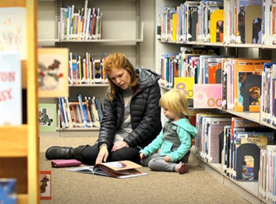 Mom and child sitting on the floor at the library looking at a book